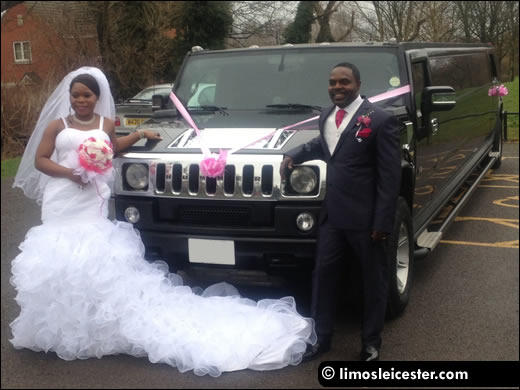 Bride and groom pose with Hummer limousine